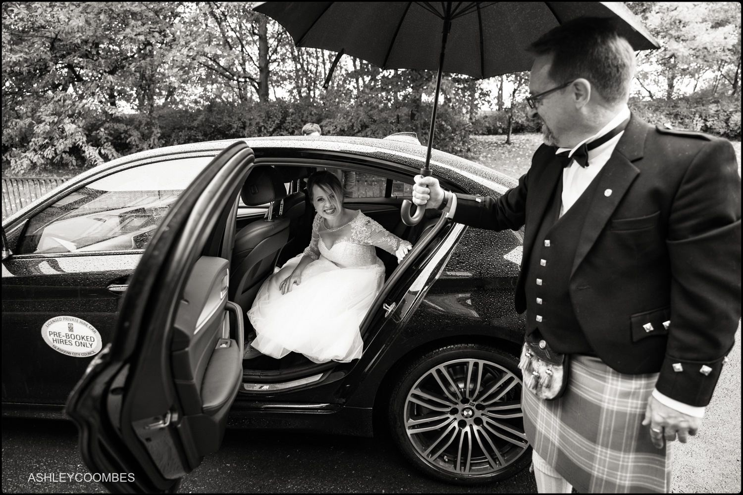 Bride getting into the car in the rain